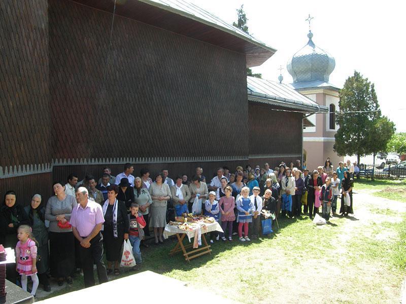 Credincioşii parohiei, participând la slujba sfinţirii altarului de vară